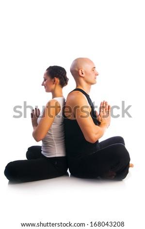 Yoga seria: Young couple in Easy Pose (Sukhasana) with Namaste mudra gesture isolated on white background - stock photo