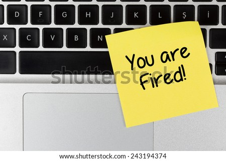 """You are Fired"" Written on Sticky Note, on Laptop Keyboard - stock photo"
