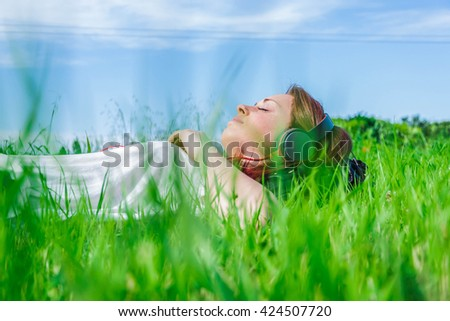 Young and caucasian woman listening to music lying on the grass, in a park - lifestyle,people, outdoor and techonology concept - stock photo