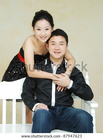 young Asian couple smiling  sitting in white chair - stock photo