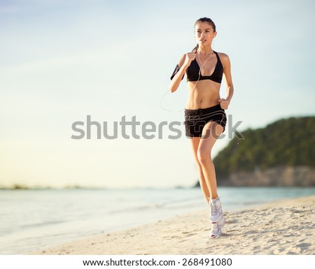 Young athlete female runs along the beach - stock photo