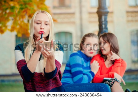Young attractive blond woman doing make up With Friends Gossiping In Background - stock photo