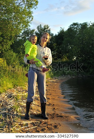 Young Attractive young mother holding a little girl in her arms at sunset light.  Walk in the autumn warm evening outdoors at sunset. Solar flare lights Woman and child.