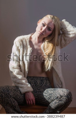 Young beautiful blonde sexy girl in wool coat and colorful pants sitting, wall background, retro look, 70s style