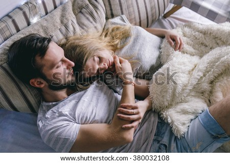 young beautiful couple embracing in bed  - stock photo