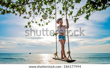 Young beautiful girl on swing  - stock photo