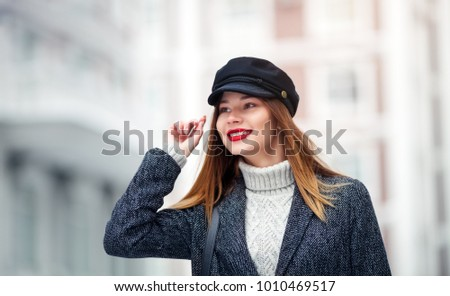 Young beautiful model in the city Close up fashion street stile portrait of pretty girl in fall casual outfit wearing fashionable glasses, red lips, elegant jacket , stylish cap.