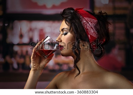 young beautiful woman with whiskey in bar - stock photo
