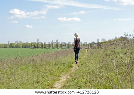 young blond beautiful woman walking on lane