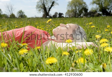 young blond woman with dandelion in mouth