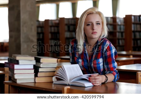 Young blonde woman sitting at the table. In the background are the rows of bookshelves. She holds in her hands an open book. Her haughty gaze directed at the camera - stock photo