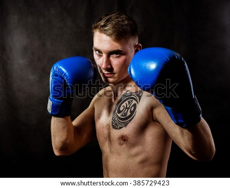 Young boxer with tattoo in front struggle . Black background
