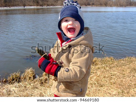 Young boy holding a rainbow trout fish caught fly fishing in a lake - stock photo