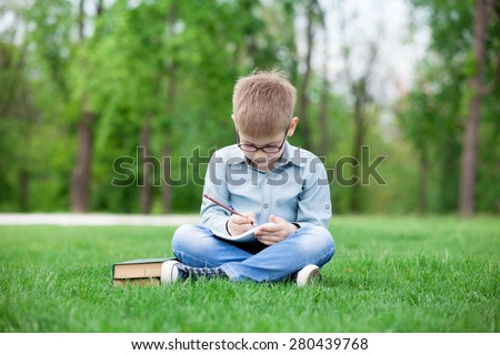 young boy with a books and notebook on green grass in the park
