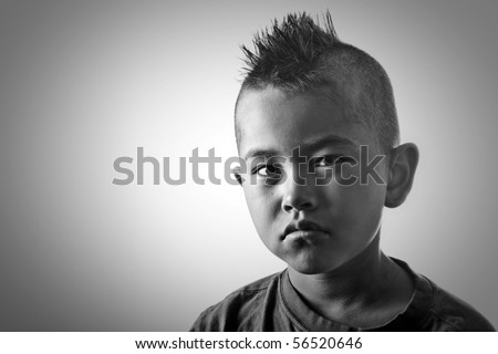 Young boy with funny mohawk haircut and serious look in black and white