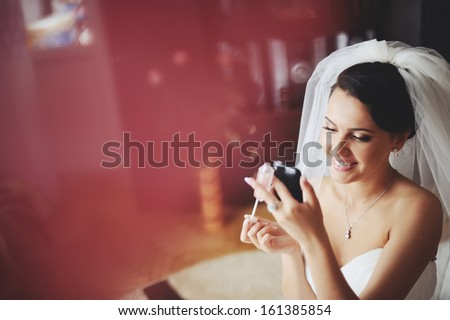 Young brunette bride having make up in the morning at home. - stock photo