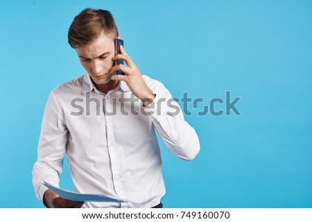 young business man talking on the phone in his hand documents on a blue background, free place