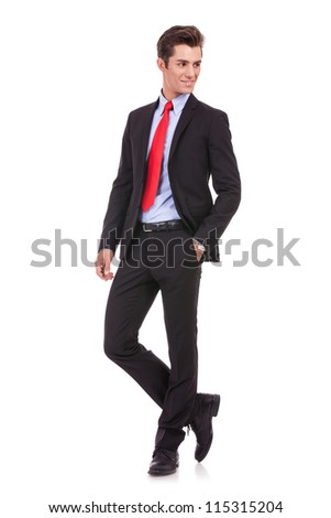 young business man with hands in pockets looking to his left side on white background. - stock photo