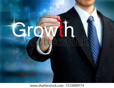 Young business man writing the word Growth with red pen - stock photo