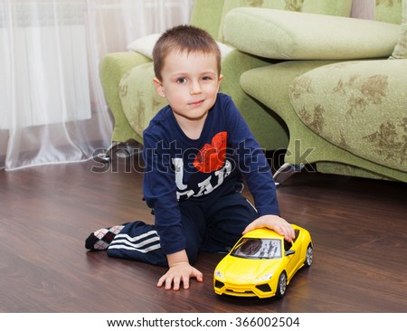 young caucasian boy plays with toy car, sitting on the floor  - stock photo