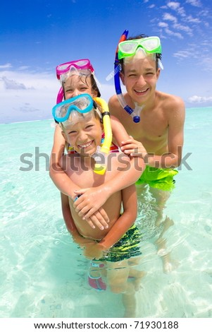 Young children snorkeling in the ocean.