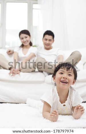 Young Chinese girl in a living room with parents in the background