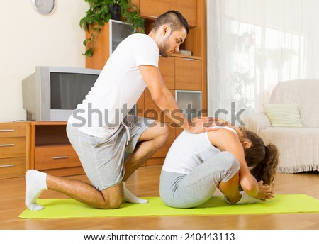 young couple doing fitness on the mat