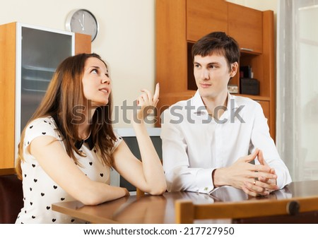 young couple having serious talking at table in living room. Focus on man