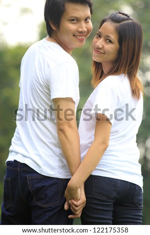 Young couple holding hands  in the park - stock photo