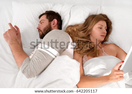 Young couple in bed looking phone and ignoring each other while lying together