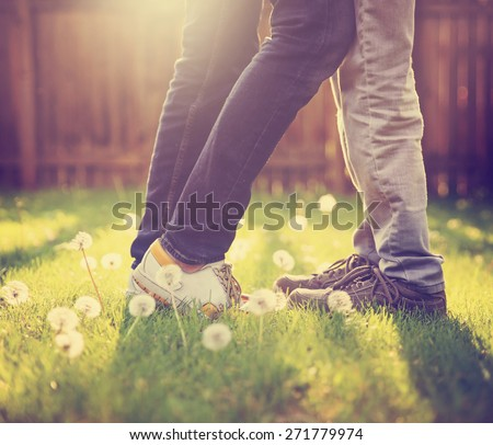 young couple kissing in a backyard in summer sun light at sunset with dandelions blooming toned with a retro vintage instagram filter app or action effect (very shallow depth of field - on the shoes) - stock photo