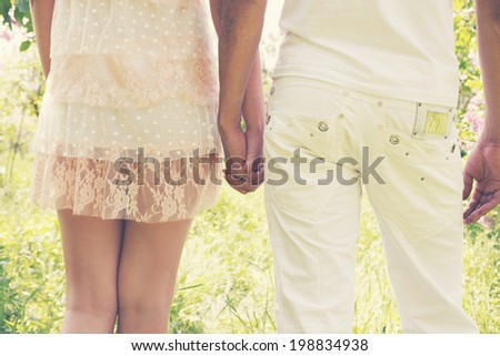 Young couple walking in the park holding hands