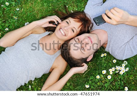 Young couple with mobile phones outdoor - stock photo