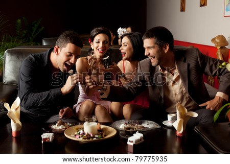 young couples changing roles, feeding ice-cream to each other - stock photo