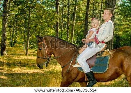 young dad daughter rolls on the horse in the woods