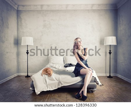 young elegant woman sitting on a bed - stock photo
