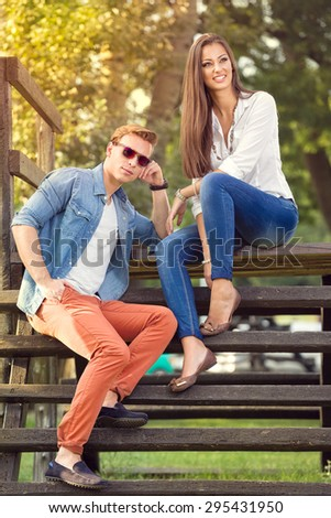 young fashion couple sitting together and relaxing in park