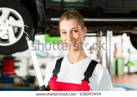 young female car mechanic looking under auto hood