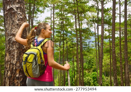 Young female hiker walking in beautiful lush pine forest nature landscape in mountains. Woman hiker wearing backpack looking at scenic pines. Hiking woman on Europe. - stock photo