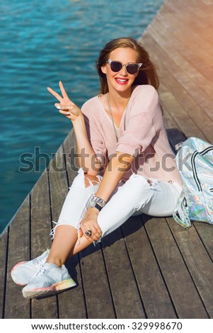 Young fresh  pretty woman sitting on  wooden pier   near sea .Active lifestyle concept. Beautiful girl in pink pastel sweater and sport sneakers  smiling  and show signs.  - stock photo