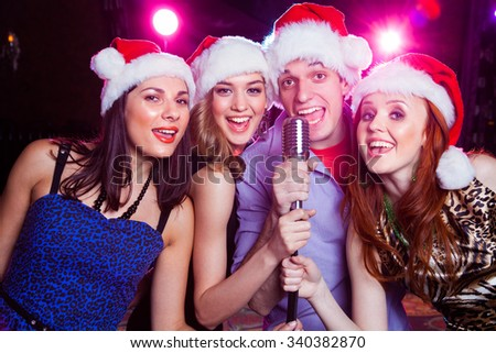 young friends in the bell Santa Claus sing karaoke microphone - stock photo