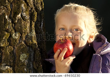 Young girl leans on tree and bite in an appel. - stock photo
