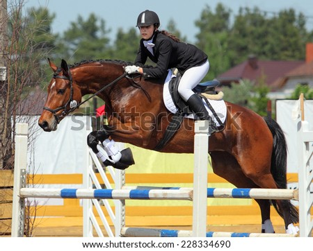 Young girl on the horse at jumping competition - stock photo