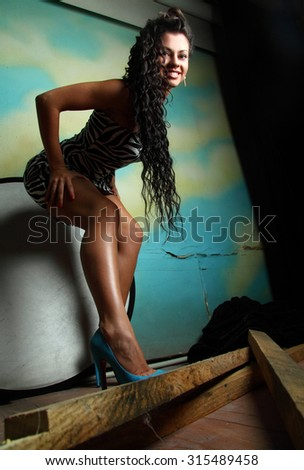 young girl with beautiful legs .  with curly hair in studio shooting .  - stock photo