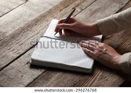 young girl writing into a book