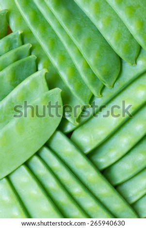 Young green peas in pods background Plant pattern made of young green peas. - stock photo