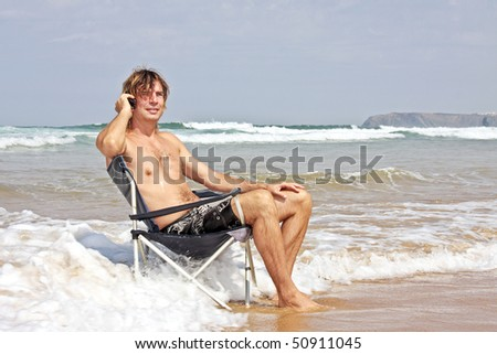 Young guy making a phone call sitting in the water from the ocean - stock photo