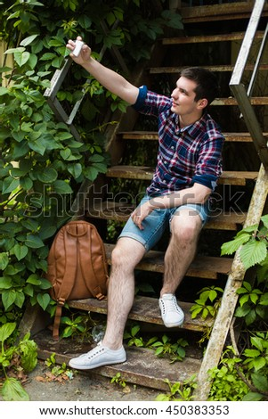 young guy sit on old stairs and donig selfie