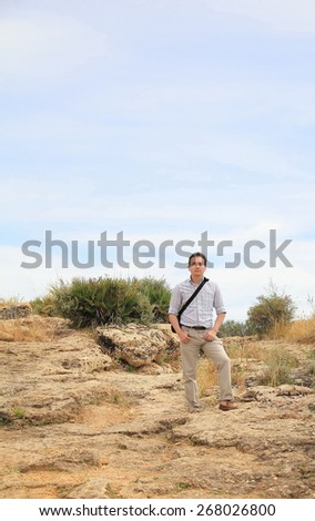 young handsome man on the background of the ruins of an ancient palace in Sicily, Italy - stock photo