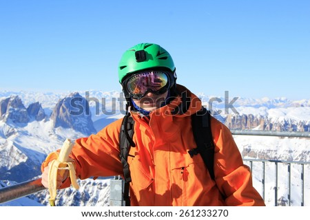 young handsome man, snowboarder in green helmet on his head and orange jacket holding a banana on a background of mountains in winter - stock photo